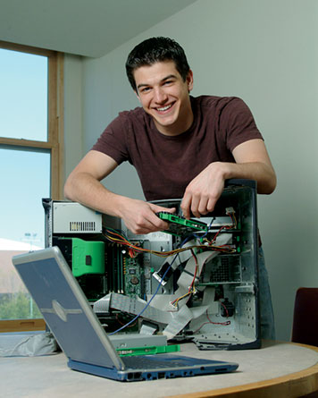 """MIT Junior Joshua Maciejewski, shown fixing his hard drive, began a computer business at 13. """"One client thought I was the assistant to the guy who was supposed to be coming. I had to explain, no one else is coming, and my Mom drove me here so we need to get moving because she has things to do."""" Photo: Ed Quinn"""