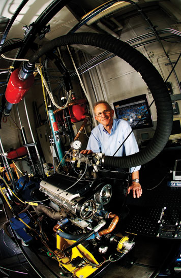 John Heywood with one of the test engines at MIT's Sloan Automotive Lab, which he directs. Photo: Len Rubenstein