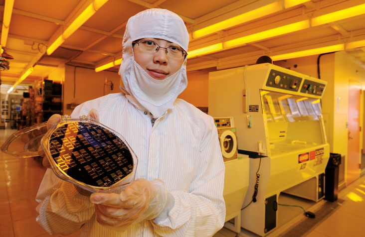 Jing Cheng (shown here in an MIT clean room) is devising high-efficiency methods for capturing the energy in waste heat from power plants and other sources. Photo: Len Rubenstein