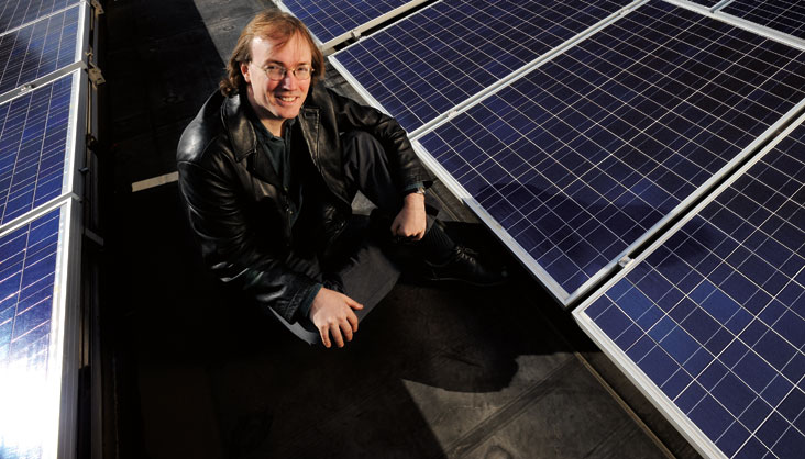 Steven Johnson (shown here with a solar array on campus) is developing ways to boost efficiency of existing solar cells. Photo: Len Rubenstein