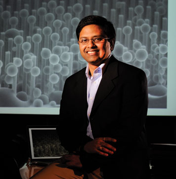 Prof. Kripa Varanasi is designing tough new nanoengineered surfaces to be used in applications ranging from energy and electronics to water purification systems. (The screen behind him shows condensation of water on a superhydrophobic surface at very small length scales.)  Photo: Richard Howard