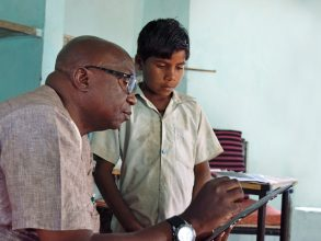 Mahuba Hazemba, senior officer of the Zambia Ministry of General Education, helps a student in Gujarat, India.