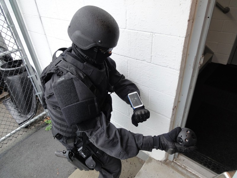 A police officer prepares to throw the Explorer into an unseen stairwell. The camera will then immediately send images of the area back to the smartphone on the officer's wrist.  Image: Courtesy of Bounce Imaging