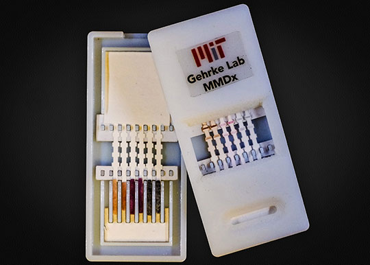 A new paper diagnostic device can detect Ebola as well as other viral hemorrhagic fevers in about 10 minutes. The device (pictured here) has silver nanoparticles of different colors that indicate different diseases. On the left is the unused device, opened to reveal the contents inside. On the right, the device has been used for diagnosis; the colored bands show positive tests.  Photo courtesy of Jose Gomez-Marquez, Helena de Puig, and Chun-Wan Yen