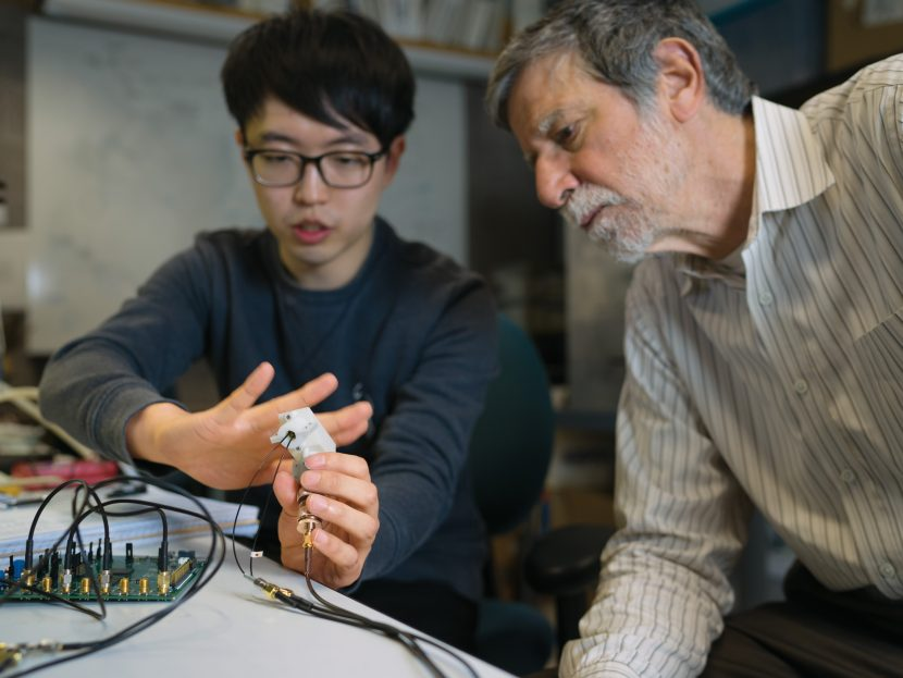 Graduate student Joohyun Seo SM'14, left, and faculty member Charles Sodini with their device for measuring arterial blood pressure. Photo: Lillie Paquette