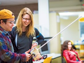 "Stefanie Mueller watches Rafael Olivera-Cintron '22 demonstrate the interactive gamin device he built to ""catch"" fish on his laptop. Photo: Gretchen Ertl"