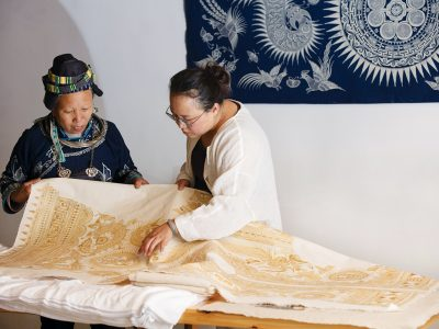 Xiao Liu, right, a community organizer with Roots Studio, looks over a batik print with an artist from Guizhou, China. Photo: 心奕