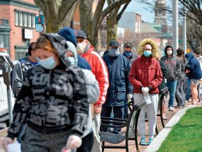 People in Chelsea, Massachusetts, one of the communities hardest hit by the coronavirus, wait in line for food distributed by the National Guard in April 2020. Photo: Joseph Prezioso / AFP via Getty IMages